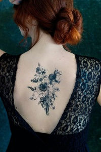 Awesome black bouquet of wildflowers tattoo on back